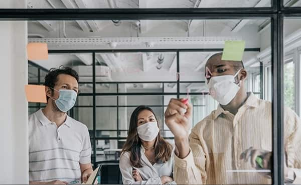 team wearing masks around a whiteboard